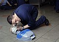 US Navy 061218-N-5275S-011 Storekeeper Seaman Jeff Rein from supply department S-1 division, practices life saving skills on a training dummy during a CPR class aboard the Nimitz-class aircraft carrier USS Dwight D. Eisenhower.jpg