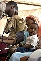 US Navy 070307-N-8154G-174 Hospital Corpsman 3rd Class Kenneth Russell listens as he takes the blood pressure of Neena, a native to Barigoni, Kenya.jpg