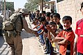 US Navy 070809-M-6412C-028 A Marine attached to Regimental Combat Team (RCT) 6 gives a line of Iraqi children high fives during Operation Alljah.jpg