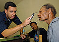 US Navy 070813-N-4954I-041 Lt. Cmdr. Matthew Behil examines a patient for cataracts while a volunteer translator stands by at Ileg Clinic near Madang.jpg