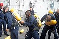 US Navy 070817-N-6775D-218 Sailors from the operations department of USS Stethem (DDG 63) participate in a self-contained breathing apparatus (SCBA) change-out race during a Damage Control Olympics.jpg