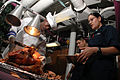US Navy 091013-N-2688M-094 Machinist's Mate Fireman Maria Cortez, right, waits for Culinary Specialist Seaman Apprentice Torrance Davis to serve her a slice of roasted pig.jpg