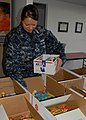 US Navy 091129-N-5812W-002 Mass Communication Specialist 1st Class Heather Ewton packs care packages at the local USO.jpg
