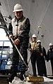 US Navy 100111-N-9928E-063 Capt. Joseph Kuzmick, commanding officer of the aircraft carrier USS John C. Stennis, dips a roller into a paint pan during a golden anchor painting ceremony.jpg