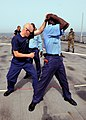 US Navy 100420-N-6676S-021 U.S. Coast Guard Machinery Technician 2nd Class David Moyer, left, demonstrates pat-down procedures on Gambia sailor Kanyi Nfanbo during a Basic Boarding Officer Course.jpg