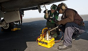 US Navy 120109-N-OY799-005 Sailors collect hydraulic fuel samples from an F-A-18E Super Hornet from the Tophatters of Strike Fighter Squadron (VFA).jpg