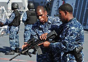 US Navy 120210-N-ED900-983 Personnel Specialist 1st Class Dwayne Smith, left, gives weapons familiarization training on the M4-A1 carbine to Operat.jpg