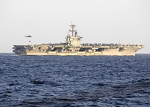 US Navy 120214-N-WD757-017 A helicopter hovers over the Nimitz-class aircraft carrier USS Carl Vinson (CVN 70) during a replenishment at sea.jpg