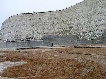 To the east of Brighton, chalk cliffs protected by a sea-wall rise from the beach. Undercliff Walk, Rottingdean - geograph.org.uk - 298484.jpg