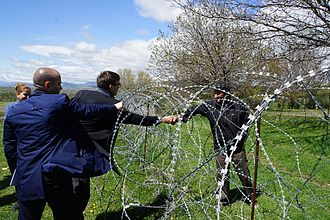 Occupied territories of Georgia - Foreign Minister of Estonia, Sven Mikser, greeting a Georgian man left behind a barbwire fence installed by the Russian military at the village of Khurvaleti in April 2017.