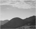 "View of hill with trees, clouded sky, ""In Rocky Mountain National Park,"" Colorado, 1933 - 1942 - NARA - 519958.tif"