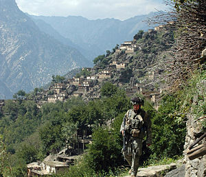 Nuristan Province - A U.S. soldier moving along a path overlooking the mountainside village of Aranas while on patrol in 2006