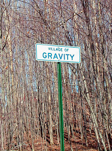 "A white sign reading ""VILLAGE OF GRAVITY"" in green lettering, with dead trees in the background."