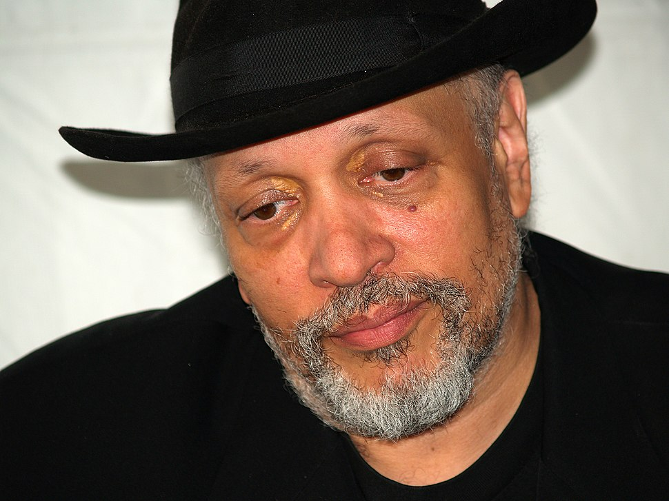 Head and shoulders of man with drooping eyelids wearing black fedora, black shirt without a collar, black jacket, and mostly grey short trimmed beard.
