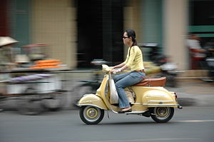 Vietnam: A young woman on a scooter.
