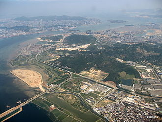 Haicang District - An aerial view of Haicang District, looking from the northwest. In the bottom left, one can see Xinyang Bridge, connecting Haicang with Jimei District (not in the pricture). Xiamen Island, connected to Haicand District by the Haicang Bridge, is in the background left; the small Gulangyu Island, to the right of it