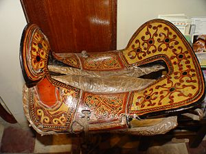 Saddle - A saddle from the Yi ethnic minority province in Yunnan province, China. Saddle has a leather base with lacquer overlay.