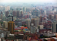 A cityscape of buildings of various heights, seen from above, gradually disappearing into a haze in the background