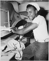 """Coast Guardsman Levern Robinson, Seaman first class, is shown at work in the ship's laundry, aboard a Coast Guard manne - NARA - 535865.tif"