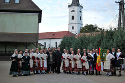 The inhabitants in traditional customes with the church tower in the background