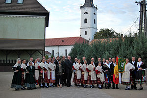 Nagykálló - The inhabitants in traditional customes with the church tower in the background