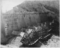 """Roosevelt Dam. View from downstream side of dam showing south spillway. Note concrete operations on aprons between... - NARA - 294505.tif"