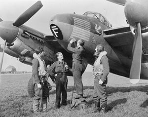 "RAF Bourn - Corporal J Patterson records the 203rd sortie on the operations tally of De Havilland Mosquito B Mark IX, LR503 'GB-F', of 'C' Flight, No. 105 Squadron RAF at Bourn, Cambridgeshire, watched by its crew, Flight Lieutenant T P Lawrenson (pilot, far left) and Flight Lieutenant D W Allen RNZAF (navigator, right). ""F-Bar for Freddie"" went on to complete 213 sorties, a Bomber Command record."