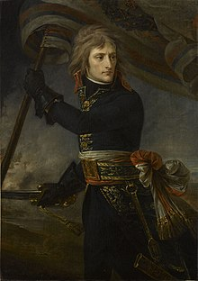 Painting depicts a clean-shaven man with long hair in a dark blue military uniform with a bright sash around his waist. He holds a sword in his right gloved hand and a flag in his left.