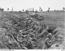 a black and white photograph of a trench with troops in it
