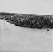 """An aerial photograph showing a barge hove-to off a wooded coastline. A cleared area of beach has been labelled in pencil with an arrow and the words """"Porton""""."""
