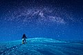 A climber climbs up a snowy slope at night.jpg
