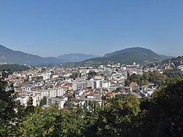 Feuillage proche, puis la ville en contrebas (beaucoup de bâtiments de 5 à 10 étages), entourée de montagnes arrondies.