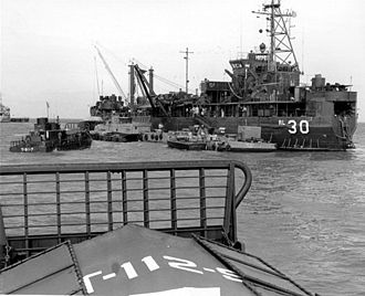 """USS Askari (ARL-30) - USS Askari (ARL-30) at anchor in Vietnam, date unknown. The ship is painted green, reflecting her assignment to the """"Brown Water Navy."""""""