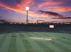 Brisbane Cricket Ground during an evening match, with the floodlights on.