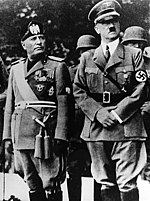Benito Mussolini and Adolf Hitler stand together on a reviewing stand during an official visit to occupied Yugoslavia.