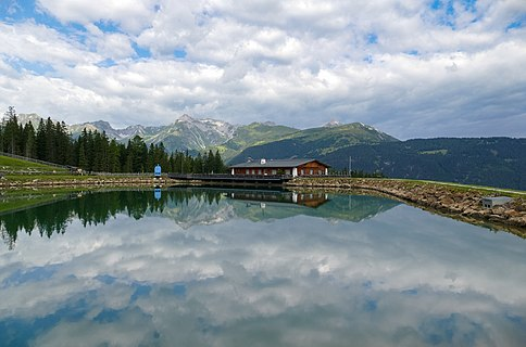 Bergeralm, Tyrol, Austria in the summer - water reservoir for artificial snow with restaurant in the background