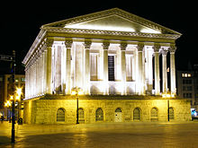exterior of large neo-classical civic building, lit up at night