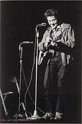 Dylan ontmoette Zijn gitaar Op het podium, lachen en Kijken naar Beneden.