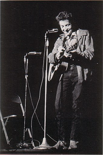 "American singer Bob Dylan has been called the ""Crown Prince"", ""King"" or ""God"" of Folk, ""The King of Folk-Rock"", ""The Jester"" and especially for his catalogue of protest songs encompassing the Vietnam War, Civil Rights and American politics: ""The Voice of a Generation"". Bob Dylan in November 1963.jpg"