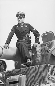 Tank Ace Michael Wittmann, wearing Waffen SS dress uniform, sits atop the main gun of his Tiger tank. The tank is covered in a ridged paste.