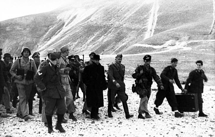 Mussolini rescued by German troops from his prison in Campo Imperatore on 12 September 1943. Bundesarchiv Bild 101I-567-1503A-07, Gran Sasso, Mussolini mit deutschen Fallschirmjagern.jpg