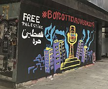 "A painted mural on a wall on a street in Girona, Spain: the Eurovision trophy appears covered in barbed wire surrounded by tower blocks, with the words ""#BoycottEurovision2019"" above, and ""Free Palestine"" in English and Arabic to the top left"