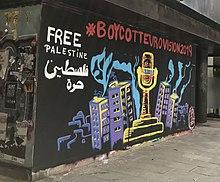 Een geschilderde muurschildering op een muur in een straat in Girona, Spanje: de Eurovisietrofee lijkt bedekt met prikkeldraad omgeven door torenblokken, met de woorden '# BoycottEurovision2019' erboven en 'Vrij Palestina' in het Engels en Arabisch linksboven