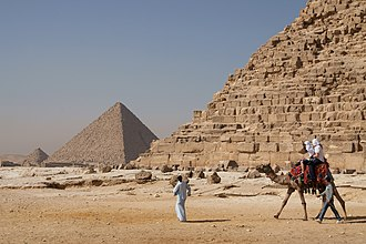 Tourists riding a Arabian camel in front of Pyramid of Khafre. The Giza Necropolis is one of Egypt's main tourist attractions. Camel and the pyramids.jpg