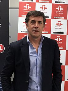 Upper body photo of Delgado in a suit standing in front of an advertising board