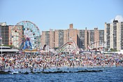 Überfüllter Strand von Coney Island mit Riesenrad und Achterbahn im Hintergrund