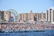 Druk Coney Island-strand met reuzenrad en achtbaan op achtergrond