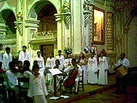 A choir and musicians dressed in white robes inside a church.