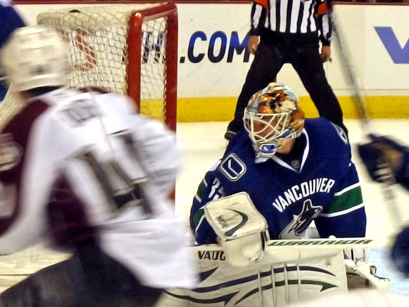 The focus is on Cory Schneider in the Canucks crease.