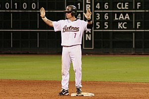 "A man in a white, pinstriped baseball uniform with ""ASTROS 7"" on the chest and a black batting helmet stands on a base with both hands raised."